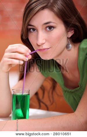 young woman dressed in green drinking a lemonade and mint cordial with a drinking straw