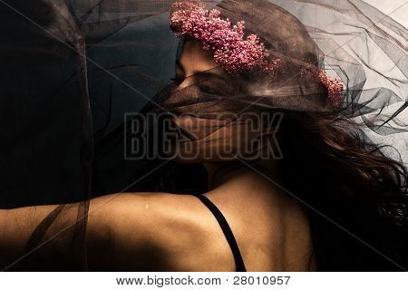 woman in dancing motion  under black veil with wreath of flowers in hair