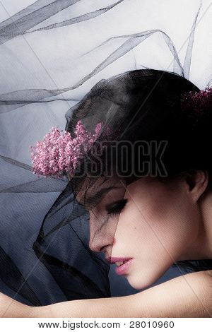 stylish beauty portrait of a woman under black veil with wreath of flowers in hair