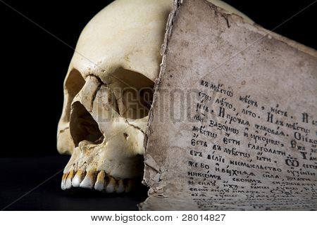 cranium and old manuscript isolated on black background