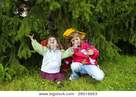Two girls sitting under in trees house