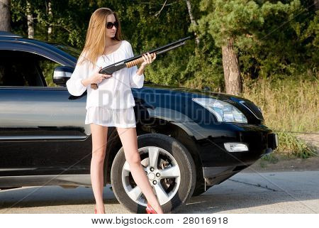 young beauty girl with gun and car