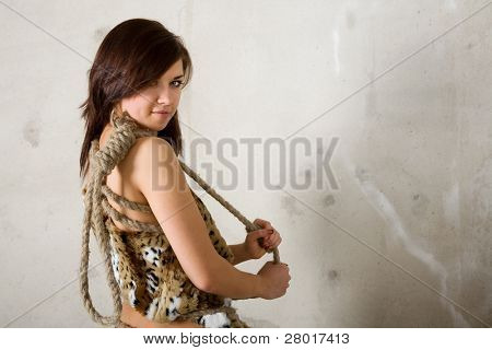 young beauty girl with rope against wall