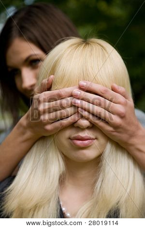 Portrait of a happy woman covering his girlfriend's eyes to surprise her