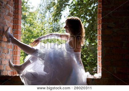 bride in white dress in building site