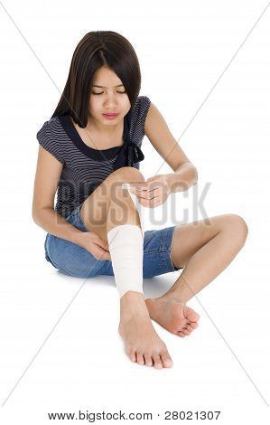 Woman Wrapping A Bandage Around Her Leg