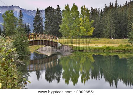 The small wooden bridge through Cascade ponds in reserve Banff in Canada