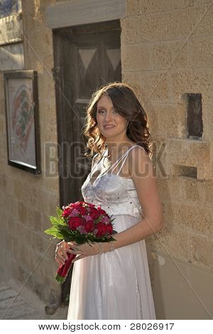 The beautiful bride with a wedding bouquet has thoughtfully leaned against a wall of old city.
