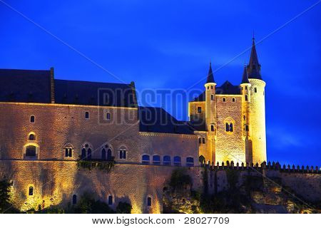 Palace of Spanish kings Alkasar in Segovia in twilight on a background of the cloudy sky