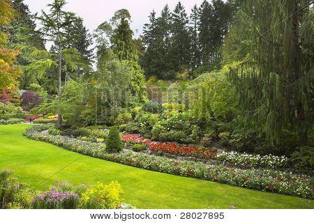 """The tourist  walks in """" Sunken garden """" well-known """"Butchard"""" garden"""