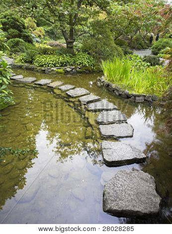 Un sendero de piedras con ladrillo a través de un fino estanque en el jardín japonés