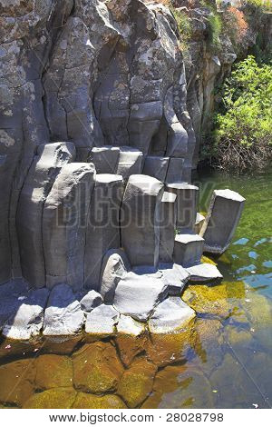 Canyon with cut basalt walls and a drying up stream
