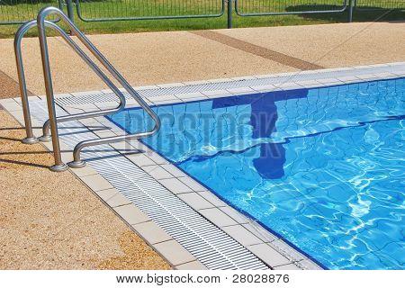 Piscina con agua transparente pura y carril de mano de la pendiente