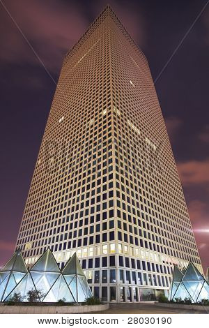 Skyscraper of the unusual triangular form in business part Tel-Aviv on a background of pink night clouds