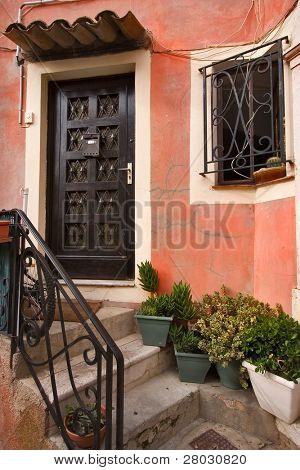 eine alte hölzerne geschnitzte Tür, ein Fenster mit einem Figur-Gitter, Steintreppen und Blumen in Töpfen