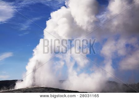 The boiling geothermal geyser in Yellowstone national park - Old Faithful. Eruption comes to an end.