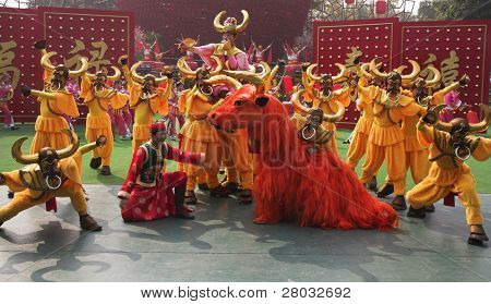 "SHENZHEN - JANUARY 22: Chinese New Year Parade. Performance of dancing ensemble in picturesque suits. An effective final stage, JANUARY 22 in ""China Folk Culture Villages"", Shenzhen, China"
