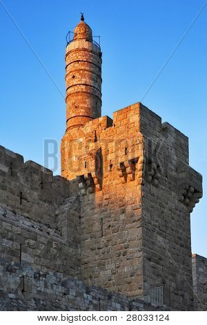 The ancient walls surrounding Old city in Jerusalem and the Tower of David, shined by the sun