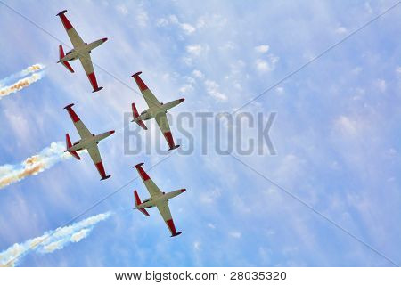 Synchronous flight of four sparkling planes on air celebratory parade