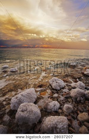 Coast of the Dead Sea in Israel in a spring thunder-storm. The coastal stones covered by salty adjournment