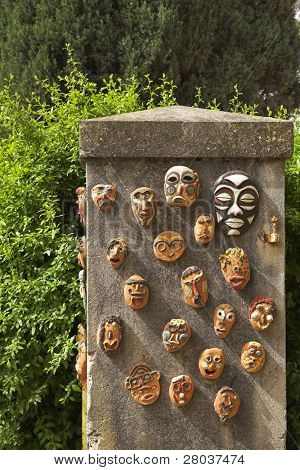 Stone curbstone in a garden, decorated ceramic ritual masks
