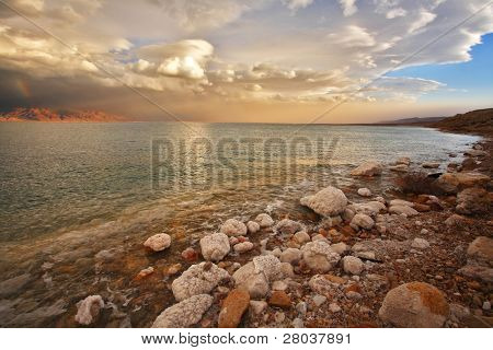 Coast of the Dead Sea in Israel in a spring thunder-storm. Coastal stones are covered by salt