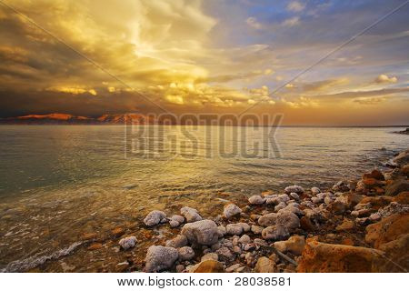 Coast of the Dead Sea in Israel in a spring thunder-storm. The coastal stones covered by salt