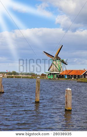 Traditional windmills and berthing bumpers on coast of the channel in Holland.