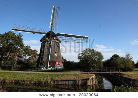 Ancient windmill on coast of a small pond. Clear autumn day in Holland