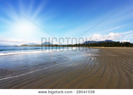 Pacific coast of Vancouver Island at sunset. Low tide exposes the wet sand