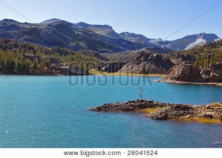 Solar midday. Magnificent azure lake and small picturesque island in park Yosemite in the USA