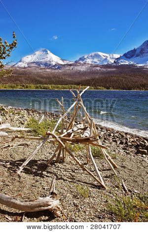 Ritual American Indian construction from white wooden bough on coast of cold mountain lake
