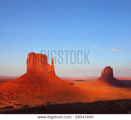 "The famous ""Mittens"" in Monument Valley. The cliffs of red sandstone at sunset"