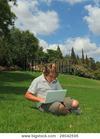A beautiful blond boy plays on the laptop on a lawn in the city park