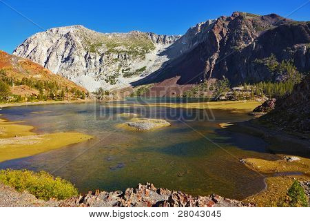 Pintoresco lago poco profundo en Pase Tioga en Parque de Yosemite en Estados Unidos. Mediodía de otoño