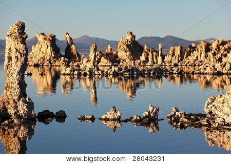 Magic sunset on Mono lake . Ancient lake in a crater of an extinct volcano. Tufa stalactites are reflected in smooth water of lake