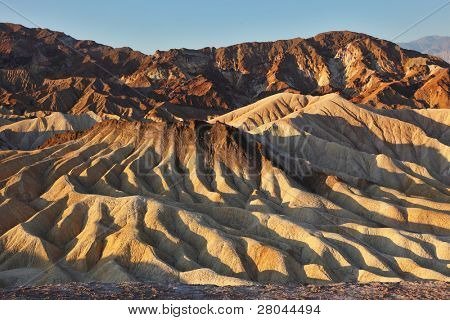 The famous section of Death Valley in California - Zabriskie Point. Picturesque hills of pink, yellow and chocolate hues at sunset
