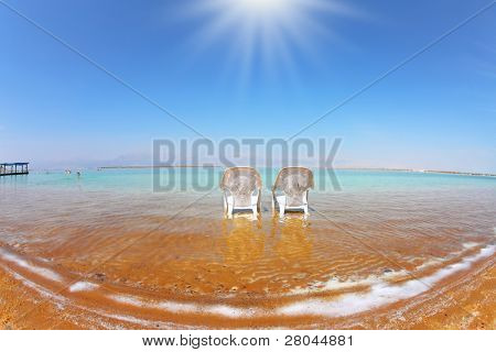 Two white beach armchairs stood side by side in the clear water. Medical beach on the Dead Sea, Israel