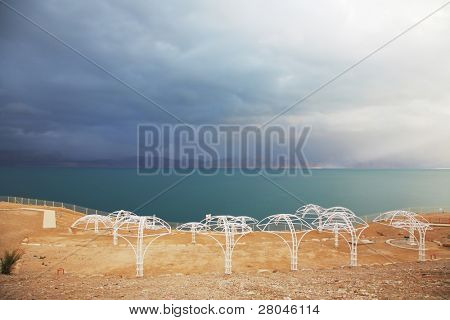 Winter on the Dead Sea. Empty beach umbrellas, green water and purple thunderheads