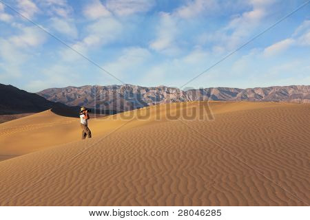 Woman photographer in a straw hat photographing sand waves. A magnificent sunrise amongst the sand dunes.