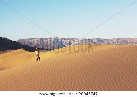 A magnificent sunrise amongst the sand dunes. Woman photographer in a straw hat photographing sand waves