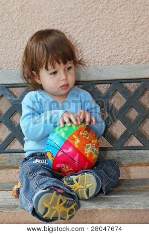 The charming thoughtful  little boy in dark blue jeans and blue sweater sits on to a garden bench with a bright multi-coloured ball in hands
