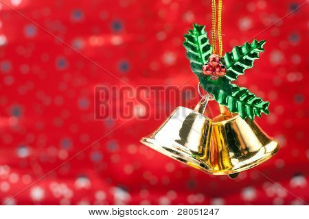 Two Gold Colored Christmas Bells Against A Holiday Background