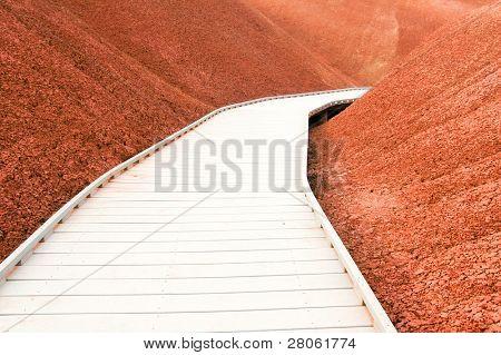 Painted Cove Trail boardwalk through dark red earth