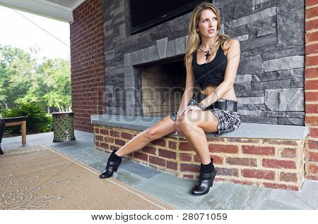 Blonde model posing in an against a fireplace in an outdoor environment
