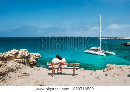 poster of Rear View Of A Couple In Love On Vacation. Honeymoon Traveller Couple Hugging On A Wooden Bench And