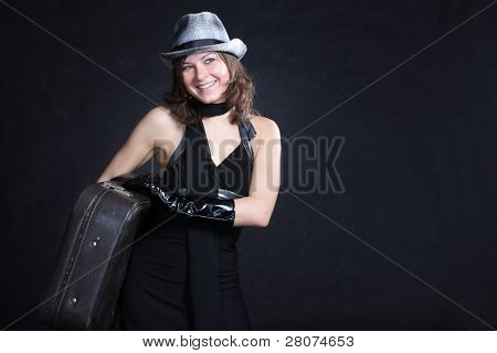 happy traveler - smiling woman with trunk in studio