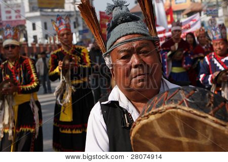 KATHMANDU, NEPAL - DECEMBER 30 2008: Nepalese caste Gurung celebrate their traditional New Year. Procession in traditional costumes goes around the city. Men beat the drums, women dance.