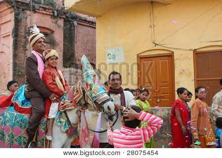 HARIDWAR, INDIA - JANUARY 14: The groom goes to bride, friends are dancing in front of the horse, to delay the moment of betrothal in traditional Indian wedding, January 14, 2009 in Haridwar, India.