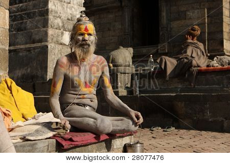 KATHMANDU, NEPAL - JANUARY 2: Sadhu (holy man) seeks alms in front of at Pashupatinath Temple on the banks of River Baghmati, January 2, 2009 in Kathmandu, Nepal.